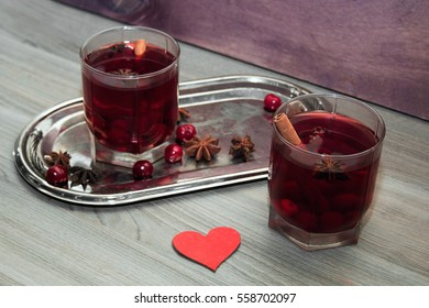 two glasses of mulled wine with cherries, cinnamon and star anise for lovers on silver vintage tray with red heart. concept for a romantic anniversary, Valentine's day