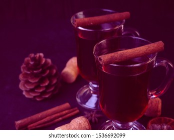two glasses of mulled wine with cinnamon and cones on a black background, horizontally for postcards in modern toning.