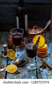 Two glasses of mulled wine with spices and orange slices, rustic style copy space