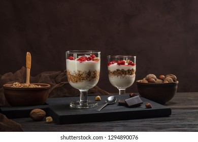 Two glasses of musli with yorurt and raspberries and nuts