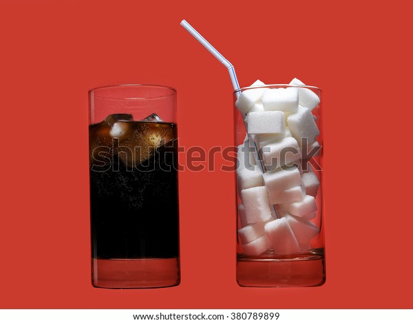 two glasses one with cola refreshing drink another full of sugar cubes and straw representing the big amount of calories content in the soda in unhealthy nutrition concept isolated on red background