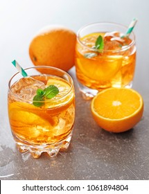Two glasses of orange coctails with mint leaves, ice and oranges on gray background