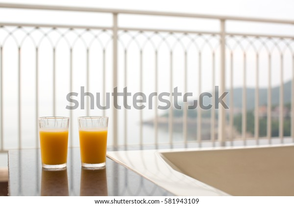 Two glasses of orange juice, beverage on a balcony overlooking nice coastal view in early morning or sunset