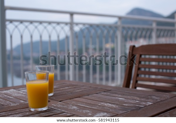 Two glasses of orange juice, beverage on wooden table overlooking mountain and coastal view