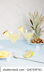 Two glasses with pineapple drink. Glasses are decorated with slices of pineapple and lime. In the background pineapple. Light background. Vertical frame orientation.