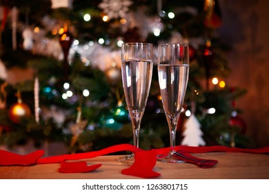 Two glasses of prosecco on a table with a Christmas tree in the background.