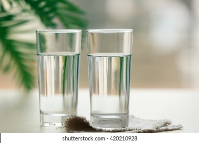 Two glasses of pure water on blurred background