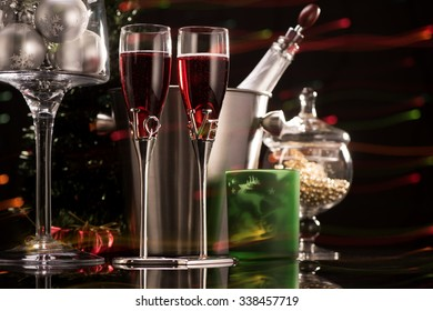 Two glasses of red champagne and Christmas decorations on colorful blurred lights background