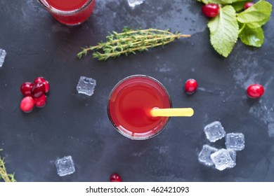 Two glasses with red cranberry lemonade on grey stone background with pepper mint, top view