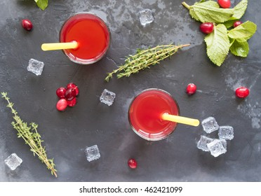 Two glasses with red cranberry lemonade on grey stone background with pepper mint and ice cubes, top view