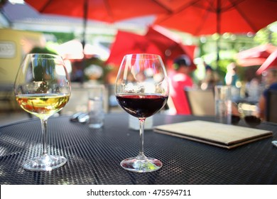 Two Glasses of Red and White Wine pair of red pinot noir and white chardonnay on beautiful patio dining table outdoors under umbrellas in the summer