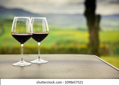 two glasses of red wine against beautiful landscape in Tuscany