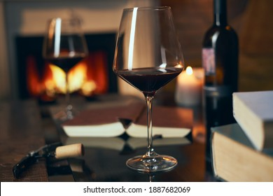 Two glasses of red wine with book on table at home, fireplace in the background. Warm, dark colors.