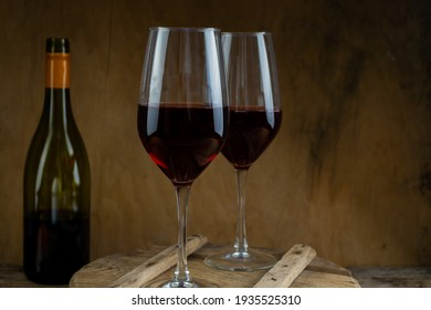 Two glasses of red wine. The bottle of wine is on the table. Wine background. Still life. Alcoholic drink in a glass. Wooden background. Copy space.