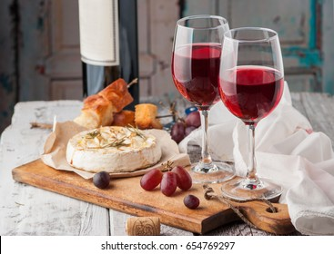 Two glasses of red wine, brie cheese with rosemary and honey sealed in the oven, skewers with croutons and fresh grapes on a white wooden table. Copy space