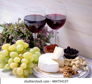 Two glasses of red wine, Camembert and heather flowers