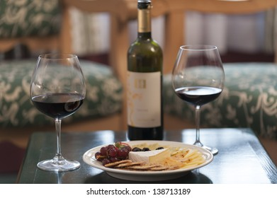 Two glasses of red wine and a cheese platter.