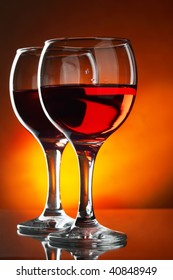 Two glasses of red wine close-up over red background