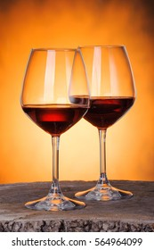 Two glasses of red wine close-up over golden background.