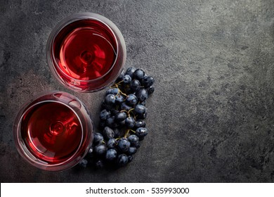 Two glasses of red wine and grapes on dark gray background from top view