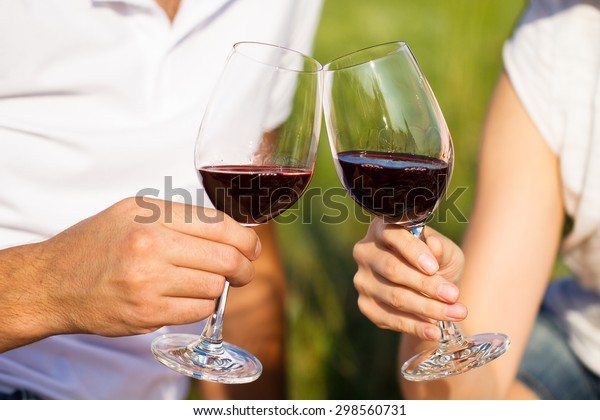 Two glasses of the red wine in hands, picnic theme