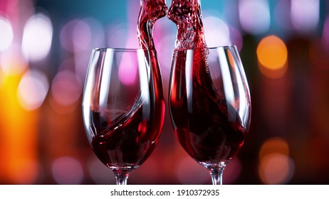 Two glasses of red wine hitting each other, blur bottles with bar counter on background