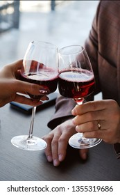 Two glasses of red wine juice. Romantic date in a cozy Italian restaurant. Man and woman clink glasses, hold . A date without alcohol. Life without alcohol. Healthy lifestyle.