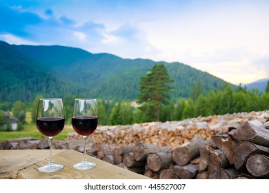 Two glasses of red wine in the mountains. Romantic evening. Carpathians, Ukraine. Eco style