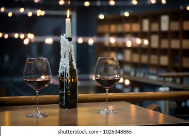 Two glasses of red wine on a table with a candle in a wine bottle. Setup in a bar in Edinburgh, Scotland