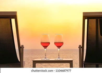 Two glasses of red wine on a background of a sea horizon in the evening. Two summer chairs and a table with two glasses of red wine at sunset. Toning