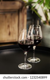 Two glasses of red wine on black table
