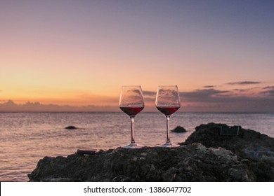 Two glasses of red wine  on the  rock beach near water. Romantic date on a beautiful sunset ocean background.  Romantic glasses of red wine against a colorful sunset.