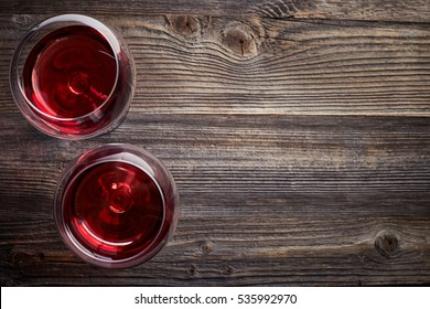 Two glasses of red wine on dark wooden background from top view