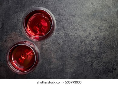 Two glasses of red wine on dark gray background from top view
