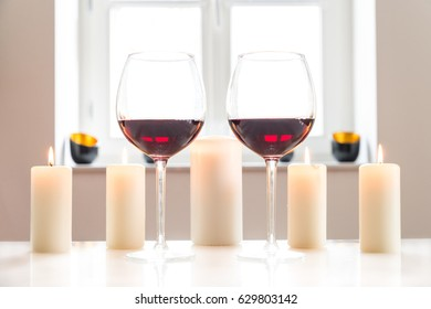 Two glasses with red wine on white table with white background and window