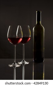 Two glasses red wine and one bottle with reflection on a dark background