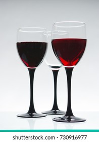 Two glasses of red wine and one empty glass.