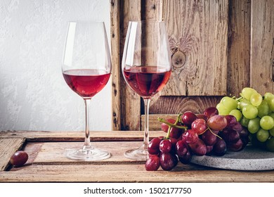 Two glasses of red wine, pink and white grapes on a wooden table.