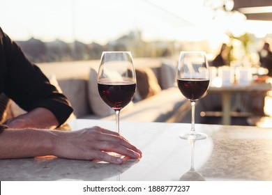 Two glasses of red wine in a restaurant, sunset light