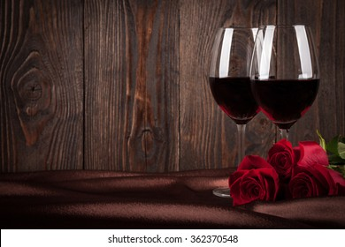 Two glasses of red wine and red roses on brown silk