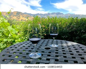 Two glasses with red wine sitting on a circular table overlooking vineyards in Napa Valley. Green vineyards in mid-ground, brown hills and blue sky in background.