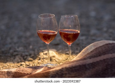 two glasses of red wine are standing on the seashore next to a blanket