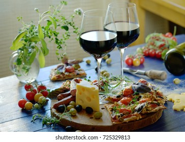 Two glasses of red wine with traditional Italian pizza.