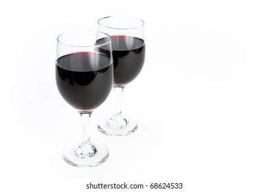 Two glasses of romantic red wine one standing in front of the other on white isolating background