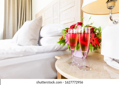 Two glasses of rose champagne in the upscale hotel room. Dating, romance, honeymoon, valentine, getaway, staycation, digital detox concepts. Horizontal