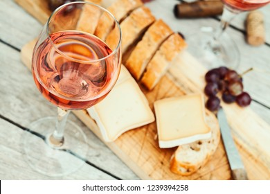 Two glasses of rose wine and board with fruits, bread and cheese on wooden table