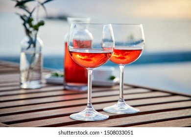 two glasses of rose wine with  olives against blue water on a pier