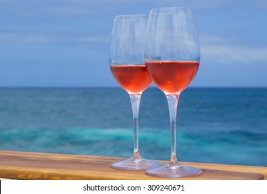 two glasses of rose wine on a wooden surface, blue ocean in the background