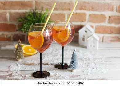 Two glasses of rossini prosecco cocktail with orange slices on wooden background with christmas decoration. Christmas party beverage.