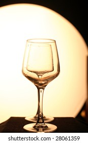 Two glasses in a row. Yellow background, dark floor. Artistic picture